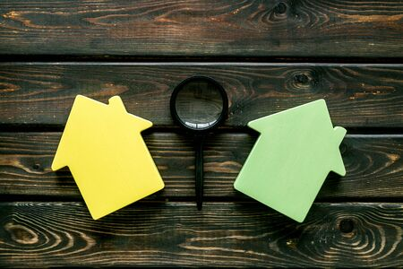 Property insurance concept with house toy and magnifier on wooden background top view