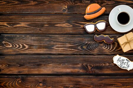 Happy Father Day with hat, glasses, moustache cookies, gift and coffee on wooden background top view mockup