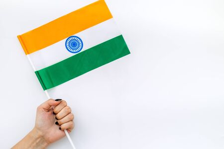 Independence Day of India concept with flag in hand on white background top view