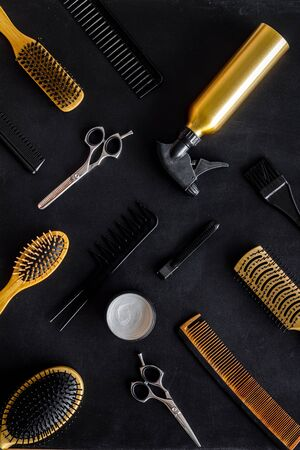 Set of professional hairdresser tools with combs and styling on black background top view pattern