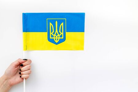 Independence Day of Ukraine concept with flag in hand on white background top view