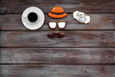愉快的父亲节与帽子,玻璃,髭曲奇饼,礼物和咖啡在木背景顶视图大模型
