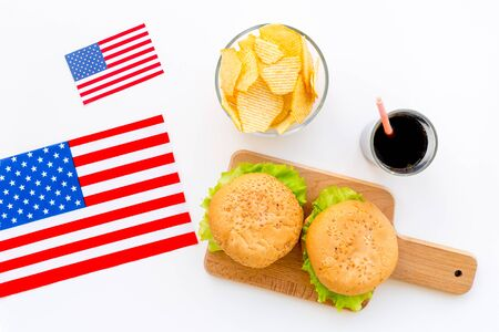 Gastronomical tourism with American flag and burgers, chips, cola on white background top view