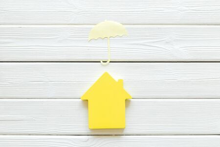 Insurance concept with house figure and umbrella on white wooden background top view