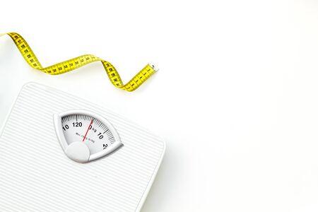 Dieetconcept met schaal en meetlint voor gewichtsverlies op witte achtergrond bovenaanzicht mock up
