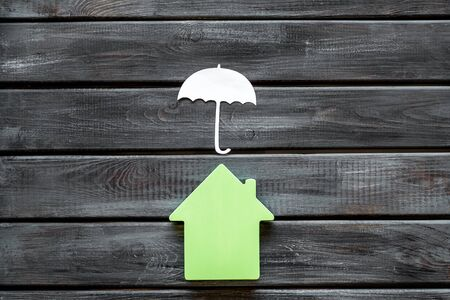 Buy and insure house concept. Insurance concept with house figure and umbrella on wooden background top view