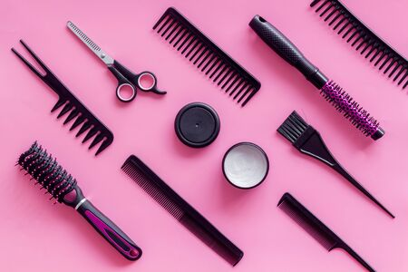 Hair style concept. Combs, scissors and hairdresser tools in beauty salon work desk on pink background top view pattern