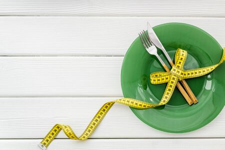 Medical starvation concept. Empty plate with fork and knife near measuring tape on white wooden background top view copy space