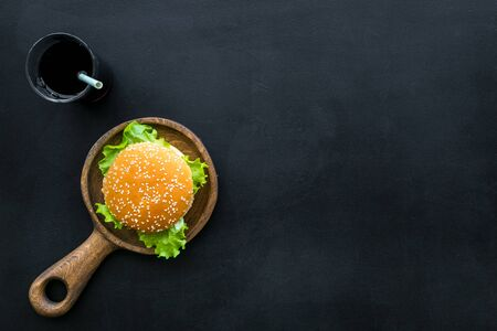 Traditional USA cuisine. National american food concept with burgers on pan and cola on black background top view space for text