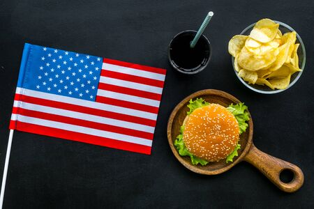 the 4th of July. Independence Day of America concept with flag, burgers, chips and coke on black background top view