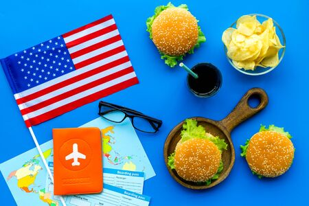 Gastronomical tourism concept with american flag, passport, tickets, map and food symbols, burgers, chips, coke on blue background top view