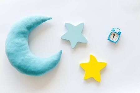 Good dream. Night sleep concept with moon, stars toy and alarm clock on white background top view