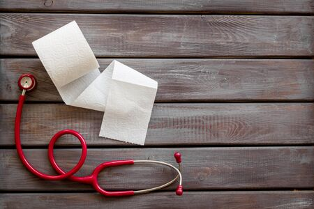 Proctology. Disease of colon concept with toilet paper roll and stethoscope on wooden background top view mockup