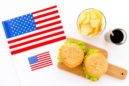 the 4th of July. Independence Day of America concept with flag, burgers, chips and cola on white background top view Banque d'images