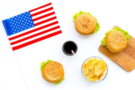 the 4th of July. Independence Day of America concept with flag, burgers, chips and cola on white background top view Stock Photo