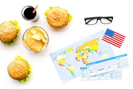 Gastronomical tourism concept with american flag, passport, tickets, map, glasses and food symbols, burgers, chips, cola on white background top view Stock Photo