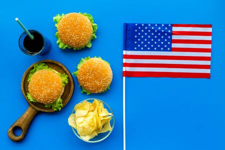 the 4th of July. Independence Day of America concept with flag, burgers, chips and cola on blue background top view