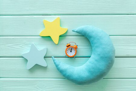 Good dream. Night sleep concept with moon, stars toy and alarm clock on mint green wooden background top view