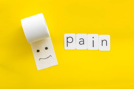 Proctology. Disease of colon concept with toilet paper roll and pain copy on yellow background top view Stock Photo