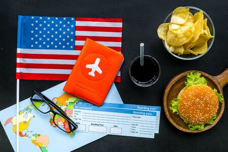 Gastronomical tourism concept with american flag, passport, tickets, map, glasses and food symbols, burgers, chips, cola on black background top view