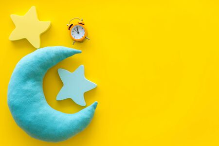 Good dream. Night sleep concept with moon, stars toy and alarm clock on yellow background top view copy space