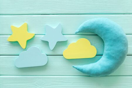 Good dream. Night sleep concept with moon, stars, cloud toy on mint green wooden background top view