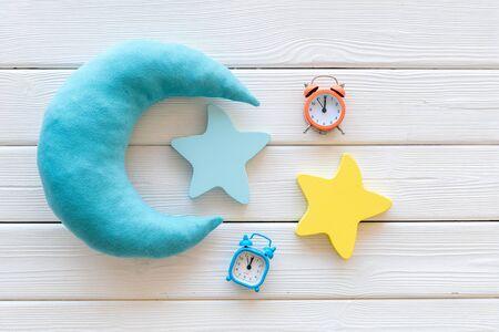 Buen sueño. Concepto de sueño nocturno con luna, juguetes de estrellas y reloj despertador en la vista superior de fondo de madera blanca