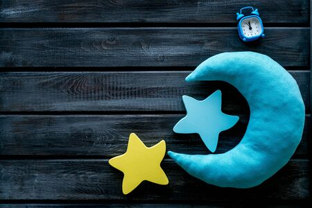 Good dream. Night sleep concept with moon, stars toy and alarm clock on wooden background top view copy space Stock Photo