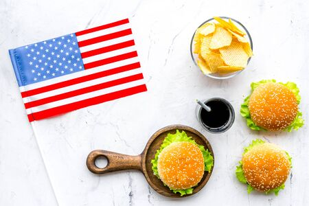 the 4th of July. Independence Day of America concept with flag, burgers, chips and cola on marble background top view