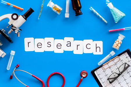 Desk of doctor. Do medical research with microscope, stethoscope, test-tubes, research copy in lab on blue background top view Stock Photo - 124932321