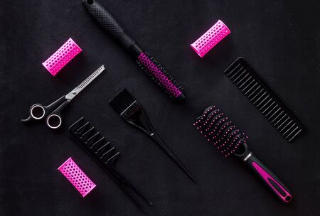 Hair style concept. Combs, scissors and pink hairdresser tools in beauty salon work desk on black background top view pattern