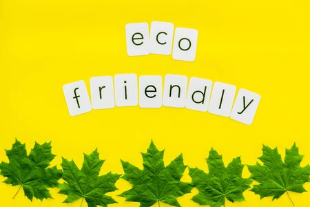 Eco friendly copy with green maple leaves for ecology concept on yellow background top view.