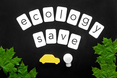 Ecology save copy with green maple leaves, car figure and lamp for eco concept on black background top view.