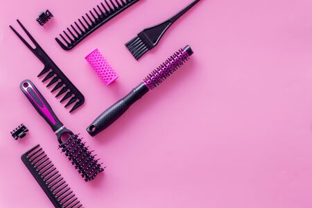 Beauty salon. Hairdresser equipment for cutting hair and styling with combs, brushes on pink background top view copyspace