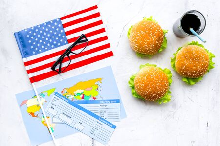 Gastronomical tourism concept with american flag, passport, tickets, map, glasses and food symbols, burgers, chips, cola on marble background top view