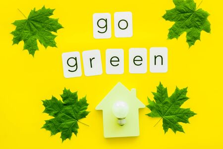 Go green copy with green maple leaves, house figure and lamp for ecology concept on yellow background top view.