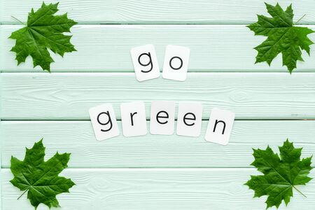 Go green copy with green maple leaves for ecology concept on mint green wooden background top view.