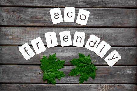Eco friendly copy with green maple leaves for ecology concept on wooden background top view.