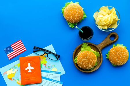 travel for traditional USA cuisine with burgers, cola, chips, passport, flight tickets, american flag and map on blue background top view