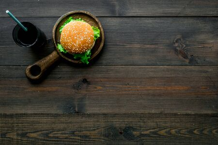 Traditional USA cuisine. National american food concept with burgers on pan and cola on wooden background top view copyspace