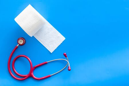 Proctology. Disease of colon concept with toilet paper roll and stethoscope on blue background top view space for text