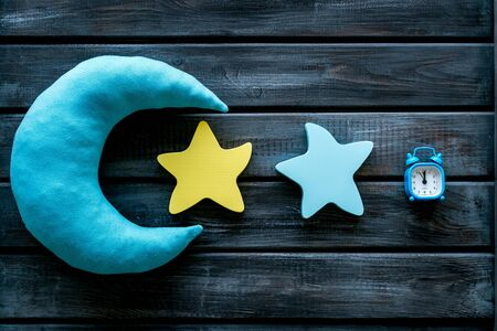 Good dream. Night sleep concept with moon, stars toy and alarm clock on wooden background top view