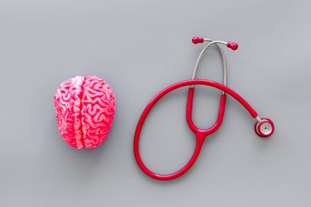 Mental specialist desk. Mental health. Disease of the brain concept with brain and stethoscope on gray background top view
