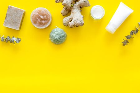 Organic set for spa. Natural herbal cosmetics with ginger on yellow background top view space for text Stockfoto