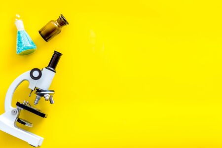 Desk of doctor. Do medical research with microscope, test-tubes in lab on yellow background top view mock-up Stock Photo