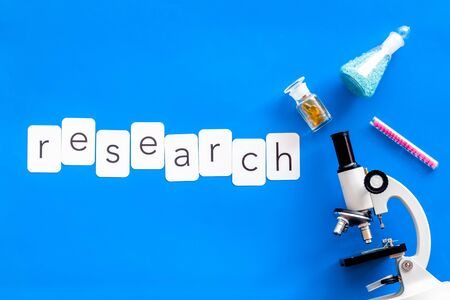 Desk of doctor. Do medical research with microscope, research copy, test-tubes in lab on blue background top view