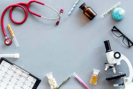 Desk of doctor. Do medical research with microscope, stethoscope, pad, pills and test tube on gray background top view mock up Stock Photo
