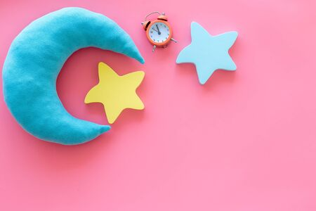 Good dream. Night sleep concept with moon, stars toy and alarm clock on pink background top view mockup Stock Photo