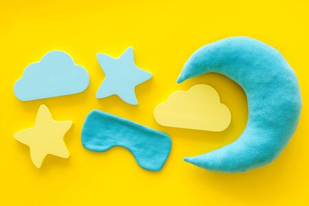 Dulces sueños. Concepto de sueño nocturno con luna, estrellas, nubes de juguete y máscara en la vista superior de fondo amarillo