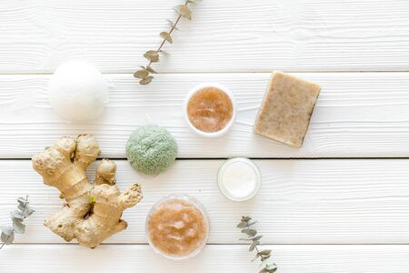 Body treatment. Cosmetics with natural herbal and ginger ingredients on white wooden background top view Imagens